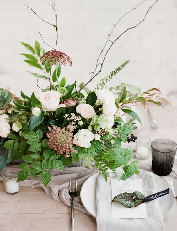 an organic winter wedding centerpiece of greenery, white and burgundy blooms and twigs