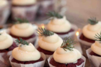 chocolate cupcakes with icing and topped with evergreens for a cozy feel at your wedding