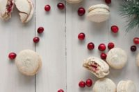 orange walnut macarons with spiced cream cheese and cranberry filling for a winter dessert table