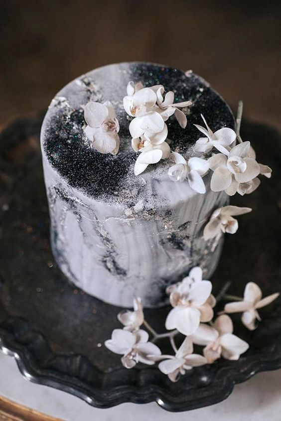 a beautiful black and white wedding cake with watercolors, silver glitter and white blooms on top looks ethereal
