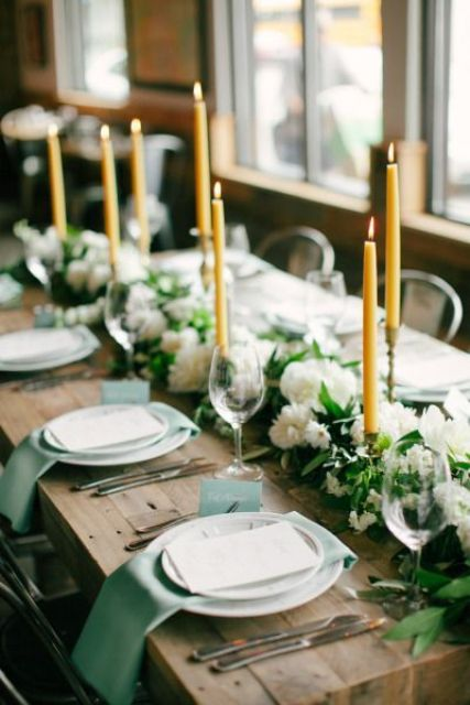 a beautiful wedding table setting with mint napkins and cards, greenery and white blooms and yellow candles