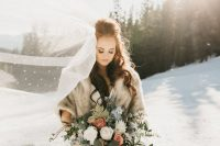 a beautiful winter bridal look with a neutral faux fur cover up and an embellished long veil is glam and chic