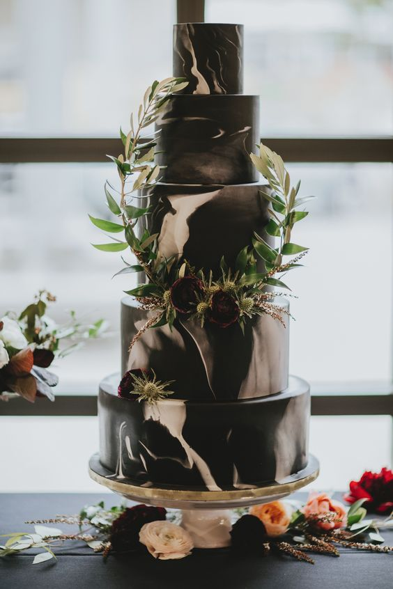 a black and white watercolor wedding cake with greenery branches, thistles and burgundy blooms