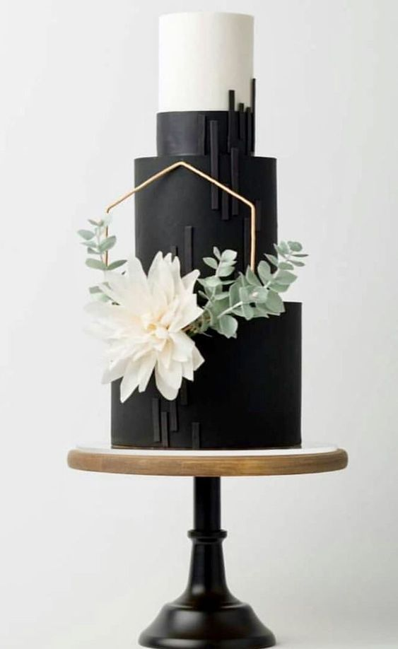 a black and white wedding cake decorated with stripes, a hexagon, a white bloom and some greenery