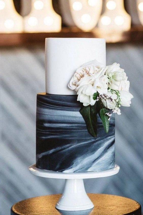 a black and white wedding cake with a white tier and a watercolor one, decorated with white blooms and greenery