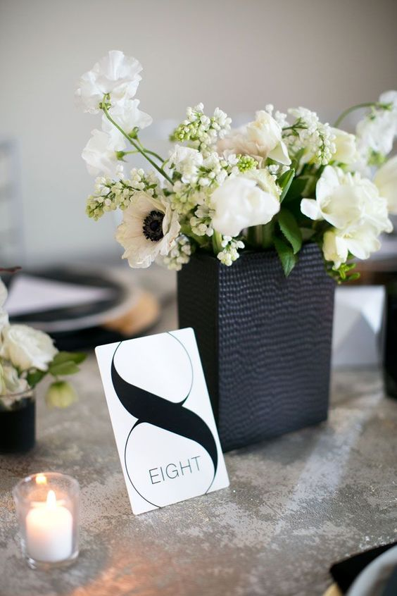 a black textural vase with lush blooms and a black and white table number