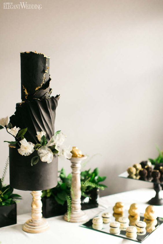 a black wedding cake with much texture and a gold rim, white blooms and greenery