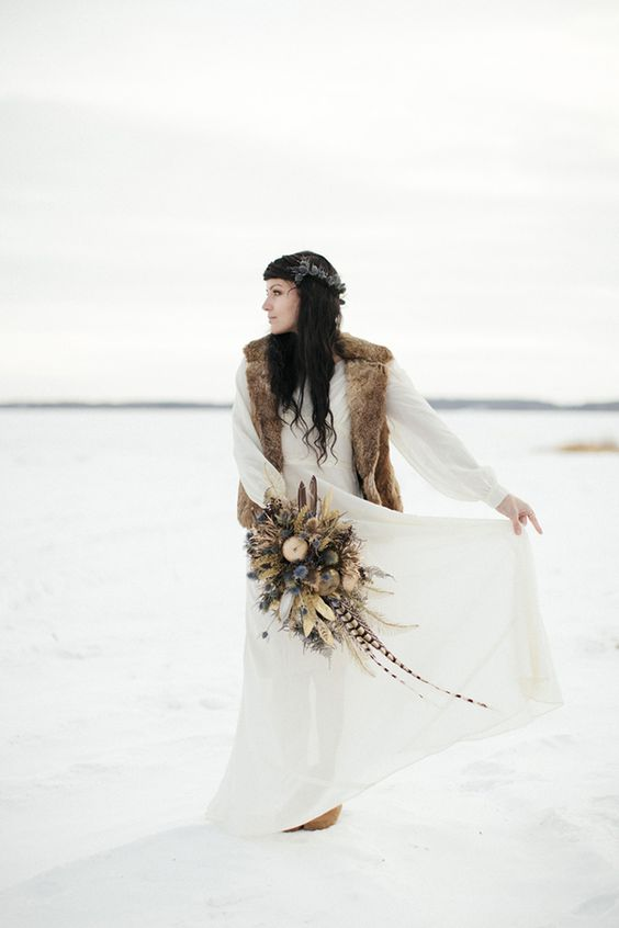 a boho winter bridal look with an A-line wedding dress with long sleeves and a beige faux fur wiastcoat plus boots