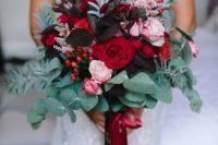 a bold and dimensional wedding bouquet with dark leaves, red and pink blooms, eucalyptus and other greenery and red ribbons