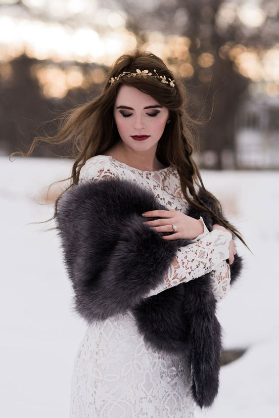a bold boho winter bridal look with a lace fitting wedding dress with a high neckline and long sleeves, a grey faux fur cove rup and a gold hairpiece