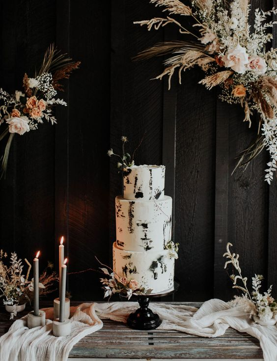 a bold modern black and white wedding cake with brushstrokes topped with dried herbs and blooms