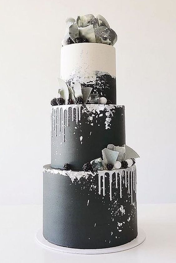 a bold modern wedding cake in black and white, with drip, blackberries, shards and a sugar bow on top