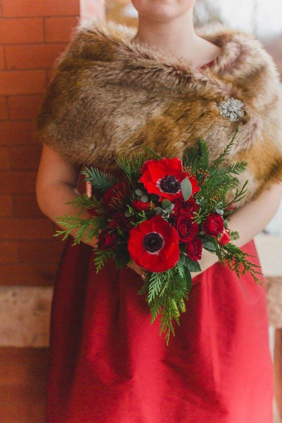 a bride rocking a red wedding gown and a chic faux fur coverup with a vitnage brooch for a statement