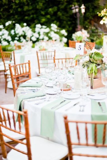 a bright summer wedding table with mint napkins, a box centerpiece with succulents and feathers plus neutrals