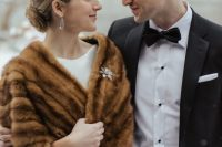 a brown faux fur stole with an embellished floral brooch to finish off the winter vintage-inspired bridal look