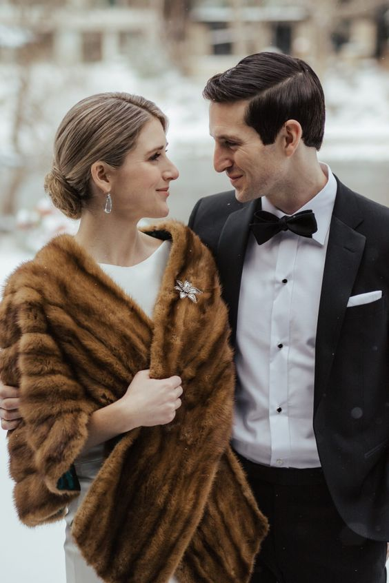 a brown faux fur stole with an embellished floral brooch to finish off the winter vintage inspired bridal look