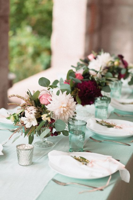 a chic and fresh wedding tablescape with a mint-colored table and glasses, bright floral centerpieces and neutral plates