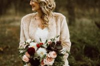a chic and refined winter bridal look with a strapless wedding ballgown with a lace bodice and a neutral faux fur cover up is cool
