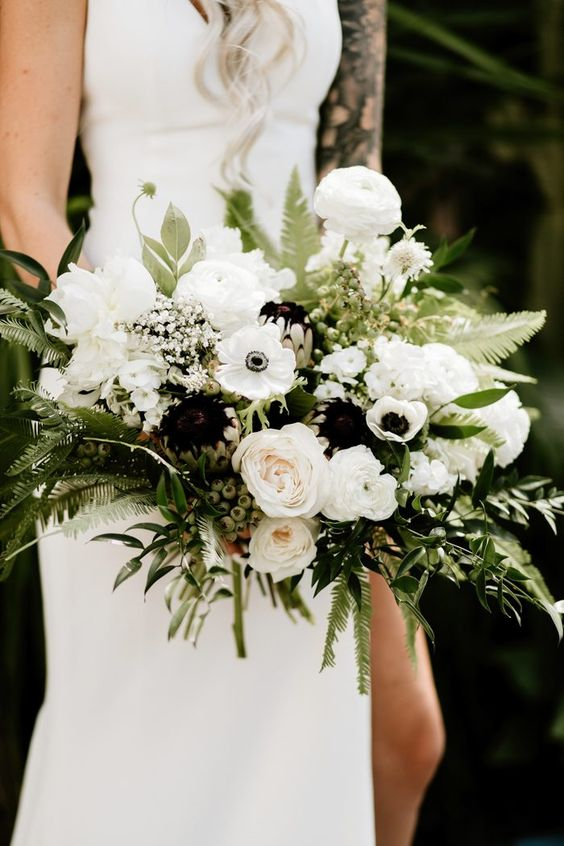 a chic black and white wedding bouquet with lush greenery is a lush and cool piece