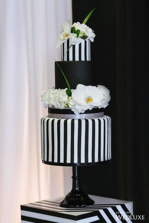 a chic black and white wedding cake with striped and a solid tier, white blooms and greenery for a whimsy touch