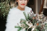 a chic embellished A-line wedding dress paired up with a white faux fur cover up and an embellished hairpiece for a Christmas bridal look