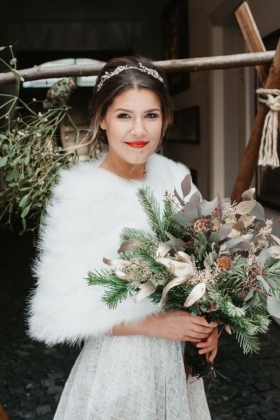 a chic embellished A line wedding dress paired up with a white faux fur cover up and an embellished hairpiece for a Christmas bridal look