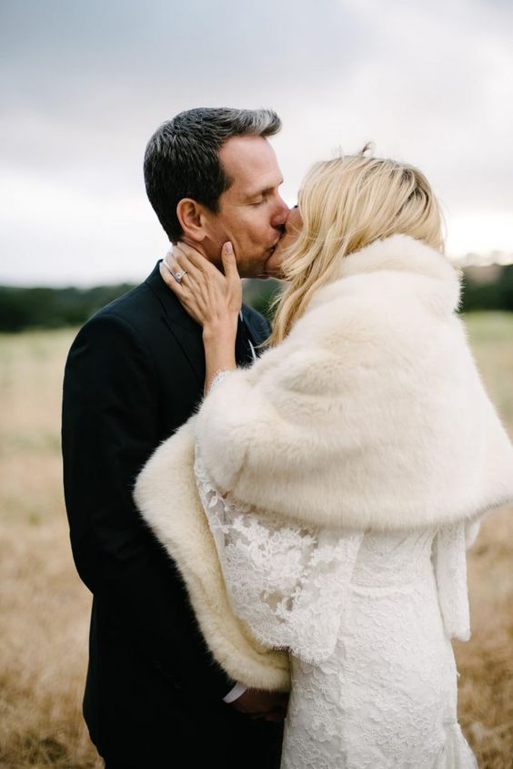 a chic lace fitting wedding dress with bell sleeves paired up with a neutral faux fur cover up for a modern romantic bridal look