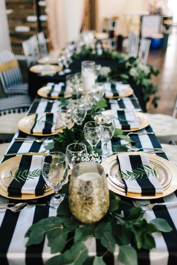 a chic modern tablescape with a striped tablecloth and napkins, much greenery and gilded touches for a touch of lux
