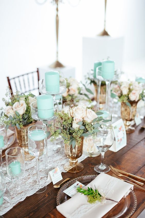 a chic vintage-inspired wedding tablescape with a lace runner, mint candles, neitral linens and pastel blooms