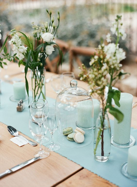 a chic wedding tablescape with a mint table runner and mint pillar candles, neutral blooms and cutlery