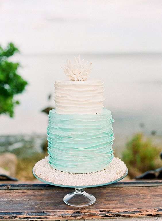 a coastal wedding cake in white and minty blue with ruffled tiers and a coral on top