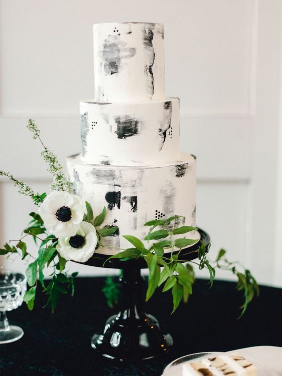 a creative black and white brushstroke wedding cake decorated with greenery and white anemones is very chic