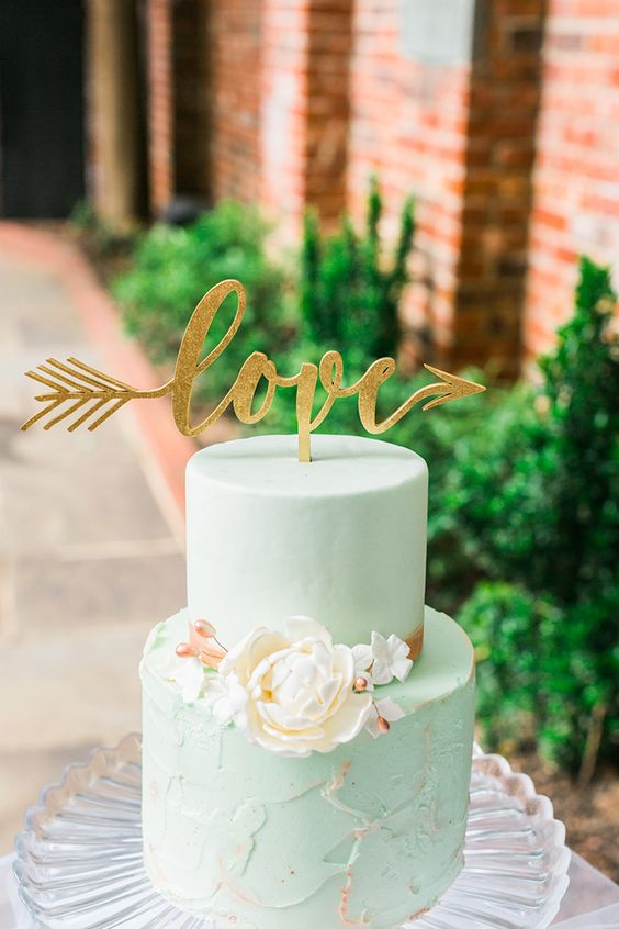 a creative mint wedding cake with a sleek and textural tier, sugar blooms and a glitter calligraphy topper