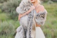 a cute winter bridal look with a lovely wedding ballgown, a grey faux fur stole and a dried flower crown
