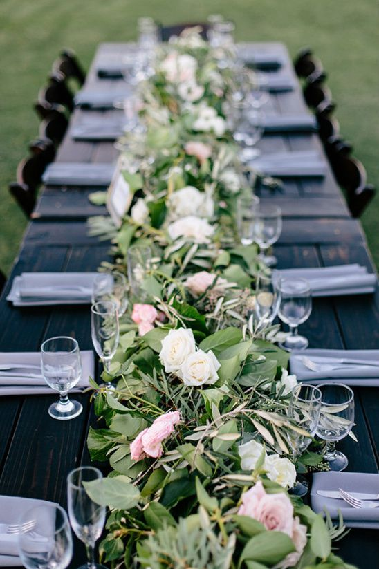 a dark stained table softened with a lush greenery and pink and white blooms table runner