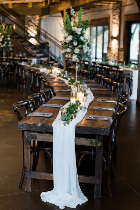 a dark stained vintage and rustic table is softened by a white runner and fresh greenery and candles on top