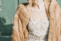 a fab winter bridal look with an embellished A-line wedding dress, statement earrings and a brown faux fur cover up is gorgeous