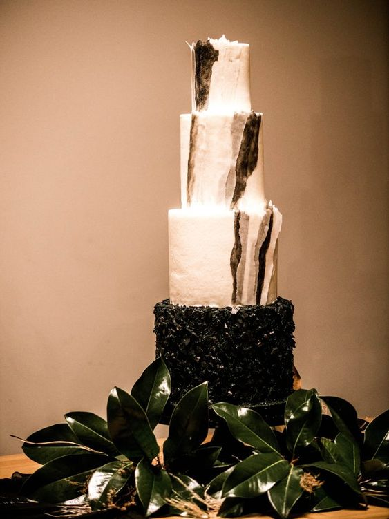 a fantastic black and white wedding cake with brushstrokes and a textural tier
