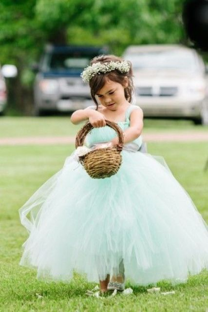 a flower girl dressed into a lovely mint blue tutu dress and a floral crown is a very cute option