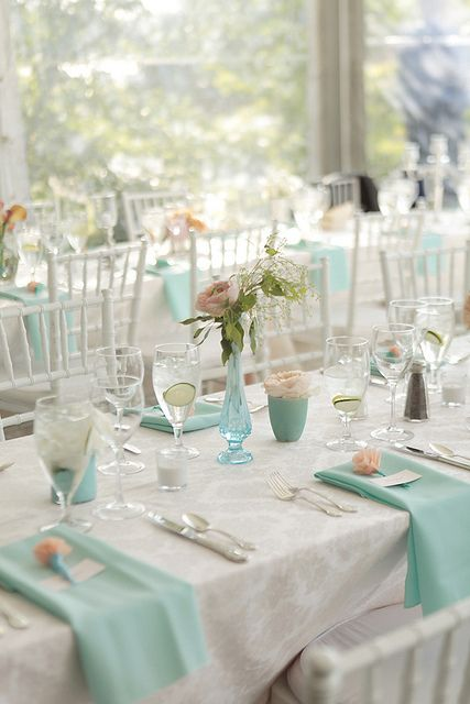 a fresh spring wedding table in white and mint blue - napkins, vases and cups with blooms