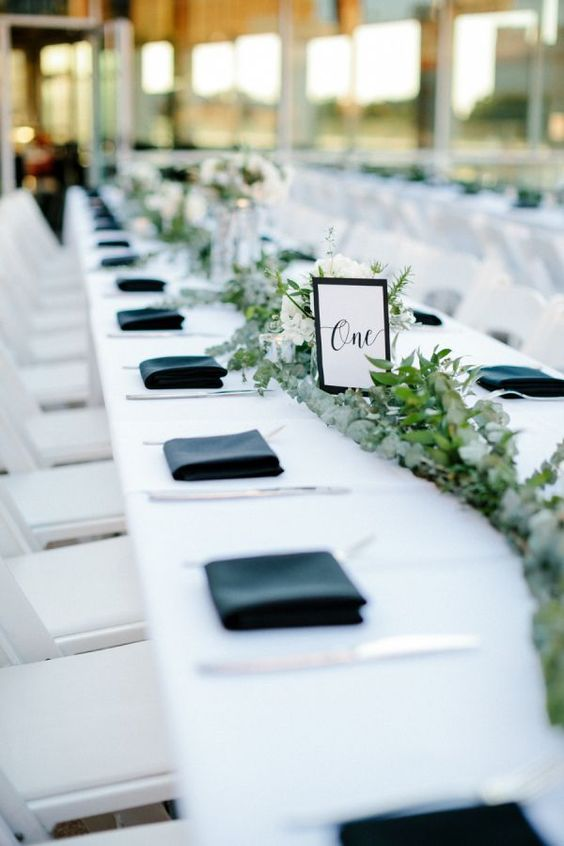 a fresh wedding tablescape with a white tablecloth, black napkins, a lush greenery and white bloom runner and a table number
