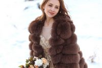 a glam gold embellished wedding dress paired with a brown faux fur jacket with short sleeves for a super glam winter bridal look