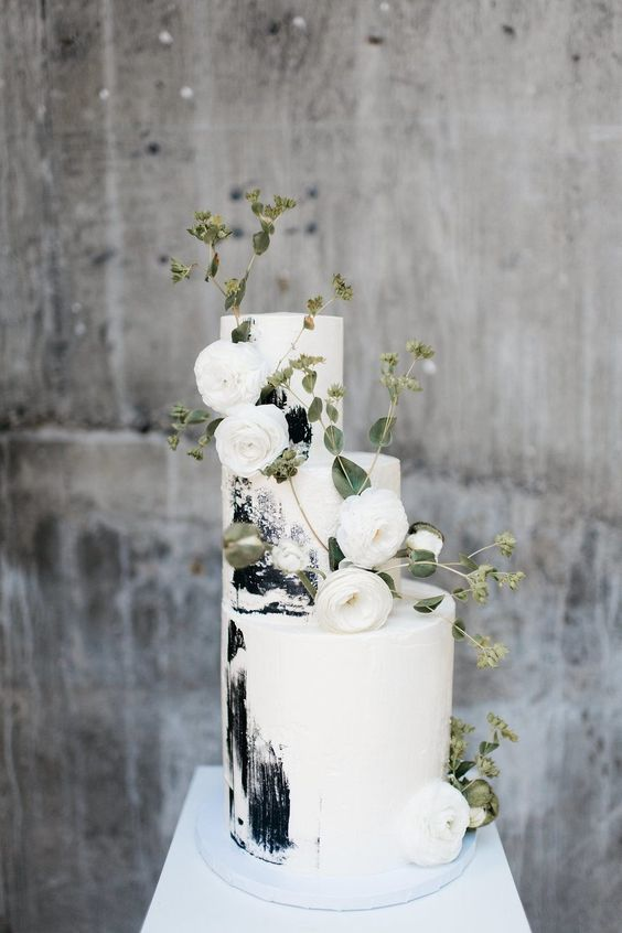 a gorgeous black and white brushstroke wedding cake decorated with white ranunculus and greenery