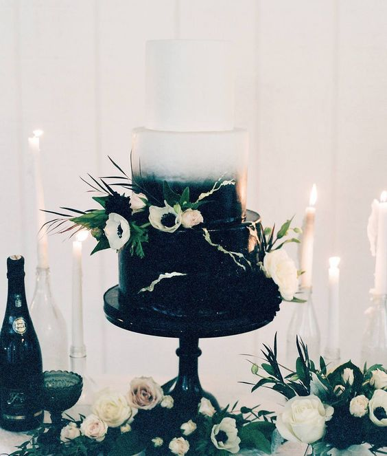 a gradient black and white wedding cake with white anemones, greenery and blush blooms is very elegant