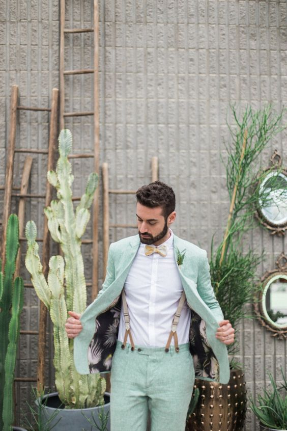 a groom wearing a mint wedding suit, a printed bow tie and suspenders looks cool and bold