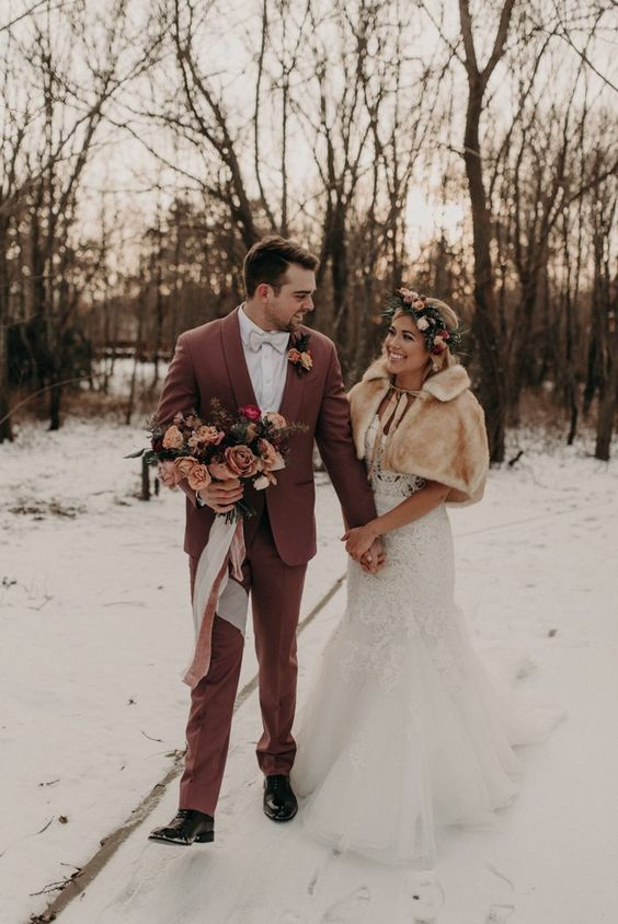 a lace mermaid wedding dress with a neutral faux fur cover up and a floral crown for a boho-inspired winter wedding