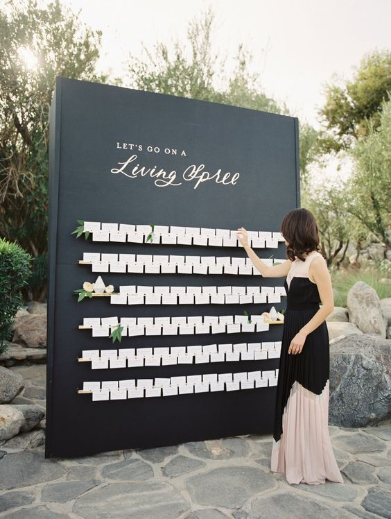 a large black seating chart with white cards and some blooms is a chic idea for a modern wedding