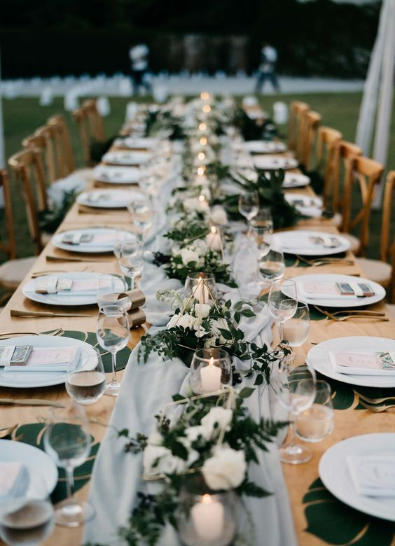 a long table spruced up with an airy grey table runner, candles in glass candle holders and lush greenery and white blooms