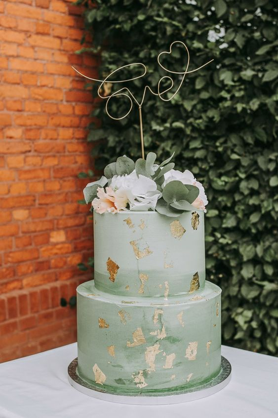 a lovely mint green brushstroke wedding cake with gold leaf and fresh blooms and greenery for a wedding