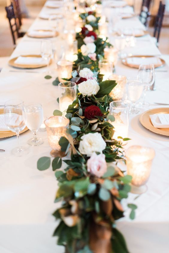 a lush floral table runner with candles will visually elongate the tables and make them bolder